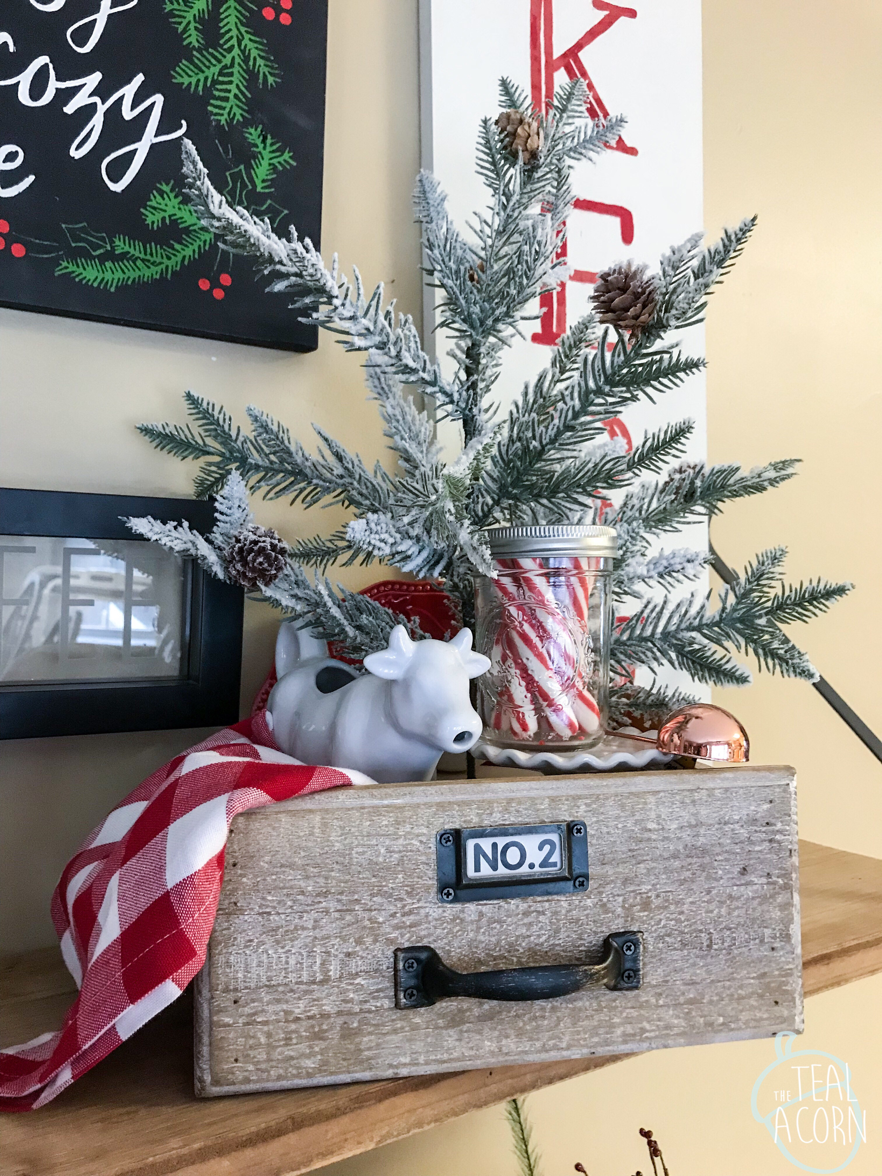 Small Christmas Coffee vignette with red and white buffalo check plaid napkin, cow creamer, peppermint sticks, and evergreen tree inside a drawer.