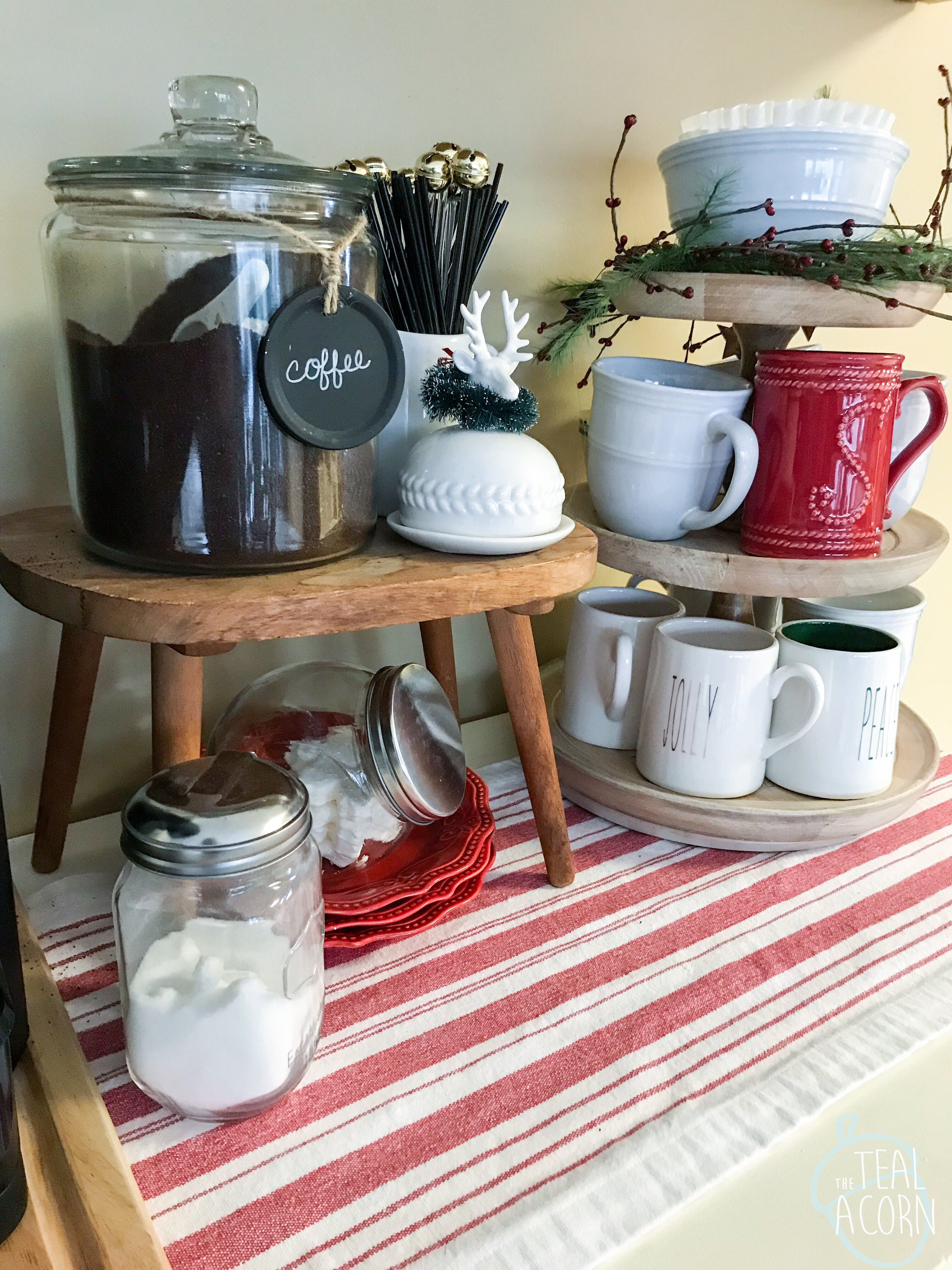 Christmas Coffee station with stack of red plates under a wooden stool used as a riser. Mary & Martha wooden tiered tray holds Christmas coffee mugs.