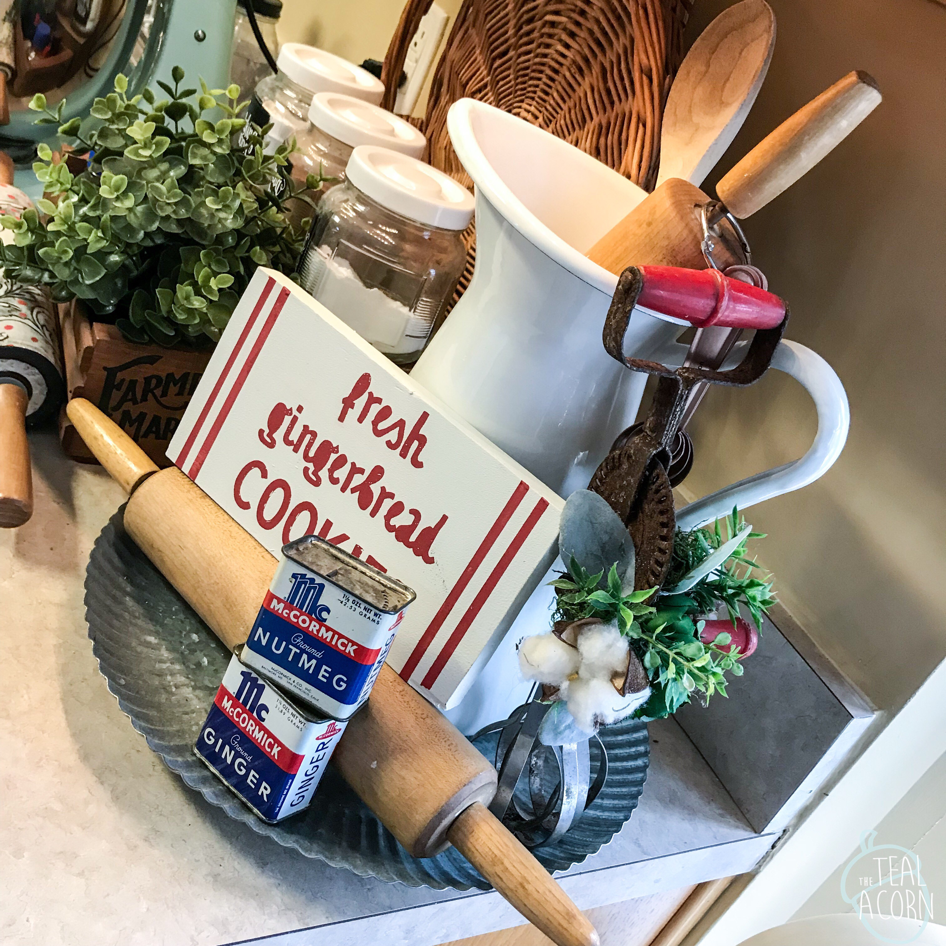 Red and white Christmas farmhouse kitchen decor. Vintage spice tins and hand mixer with cotton stem.