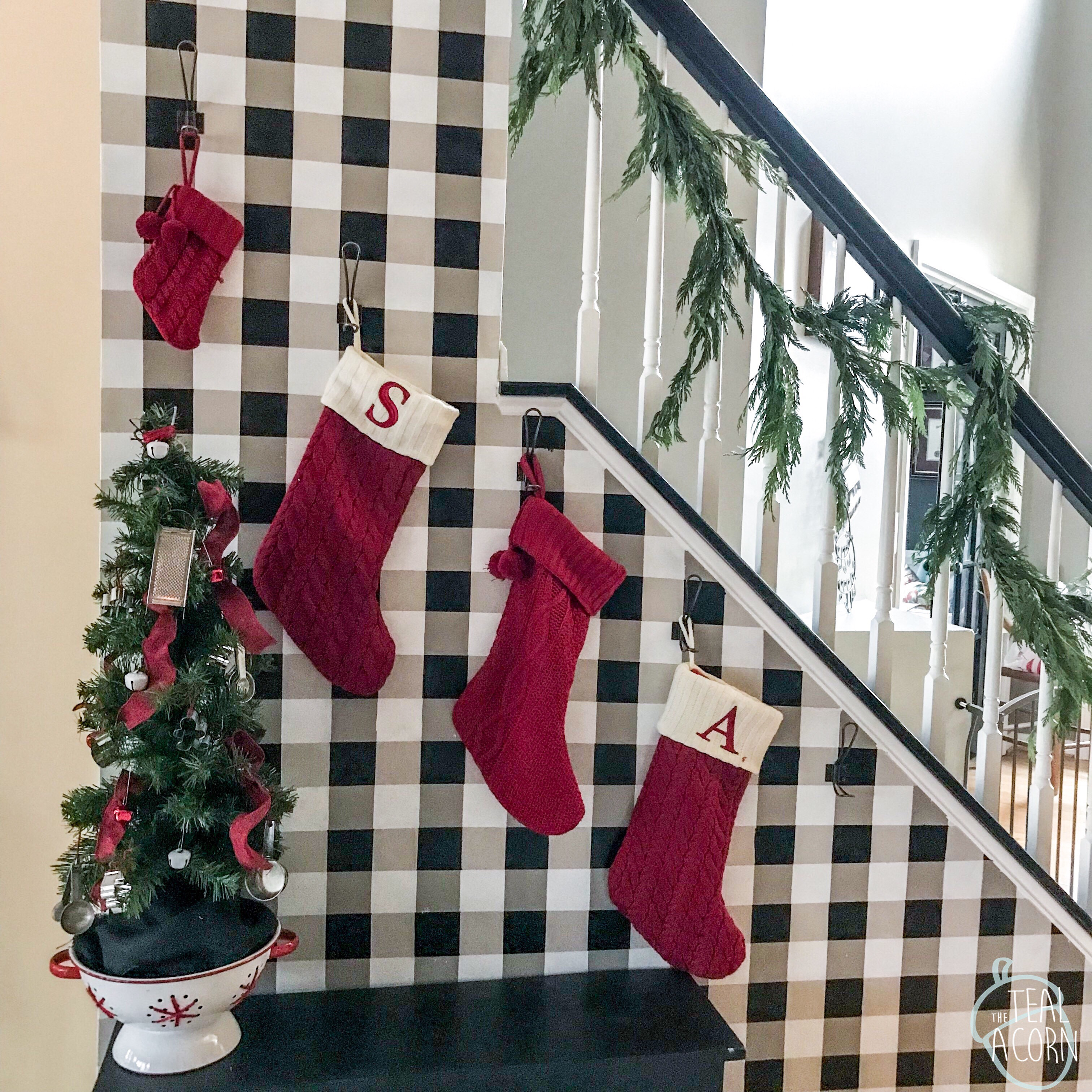 black and white buffalo check painted diy wall with red cable knit stockings, and cypress garland going down the bannister.