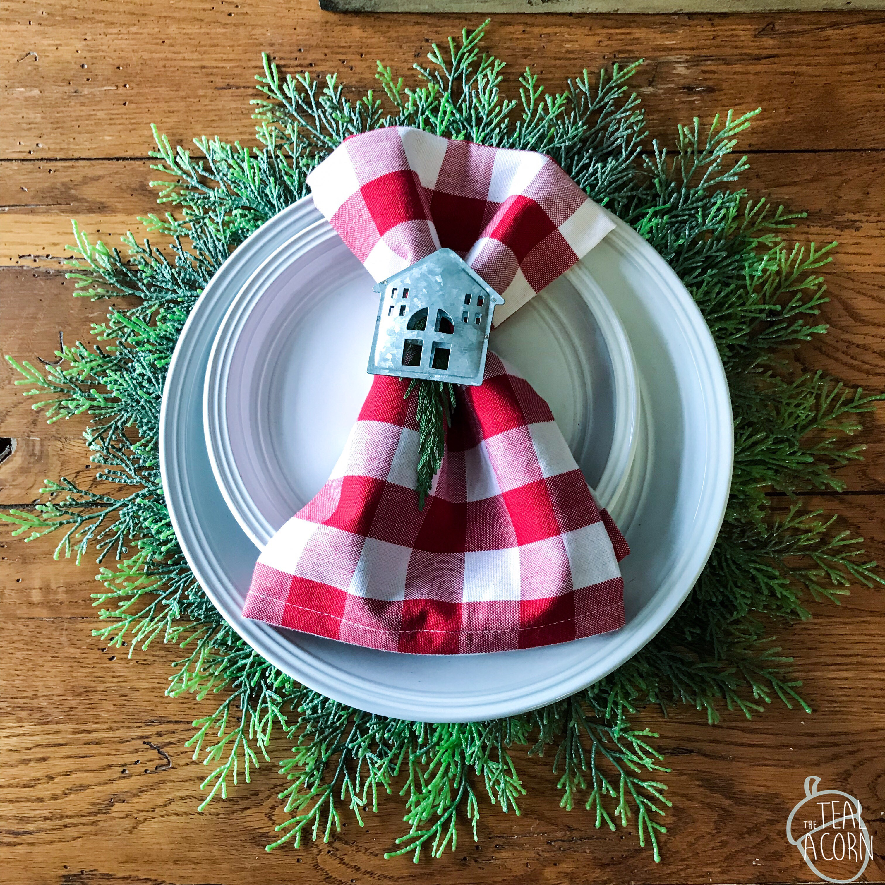 Place settings have Pier 1 cypress chargers, white plates, red and white Buffalo check plaid napkins and galvanized metal napkin rings.