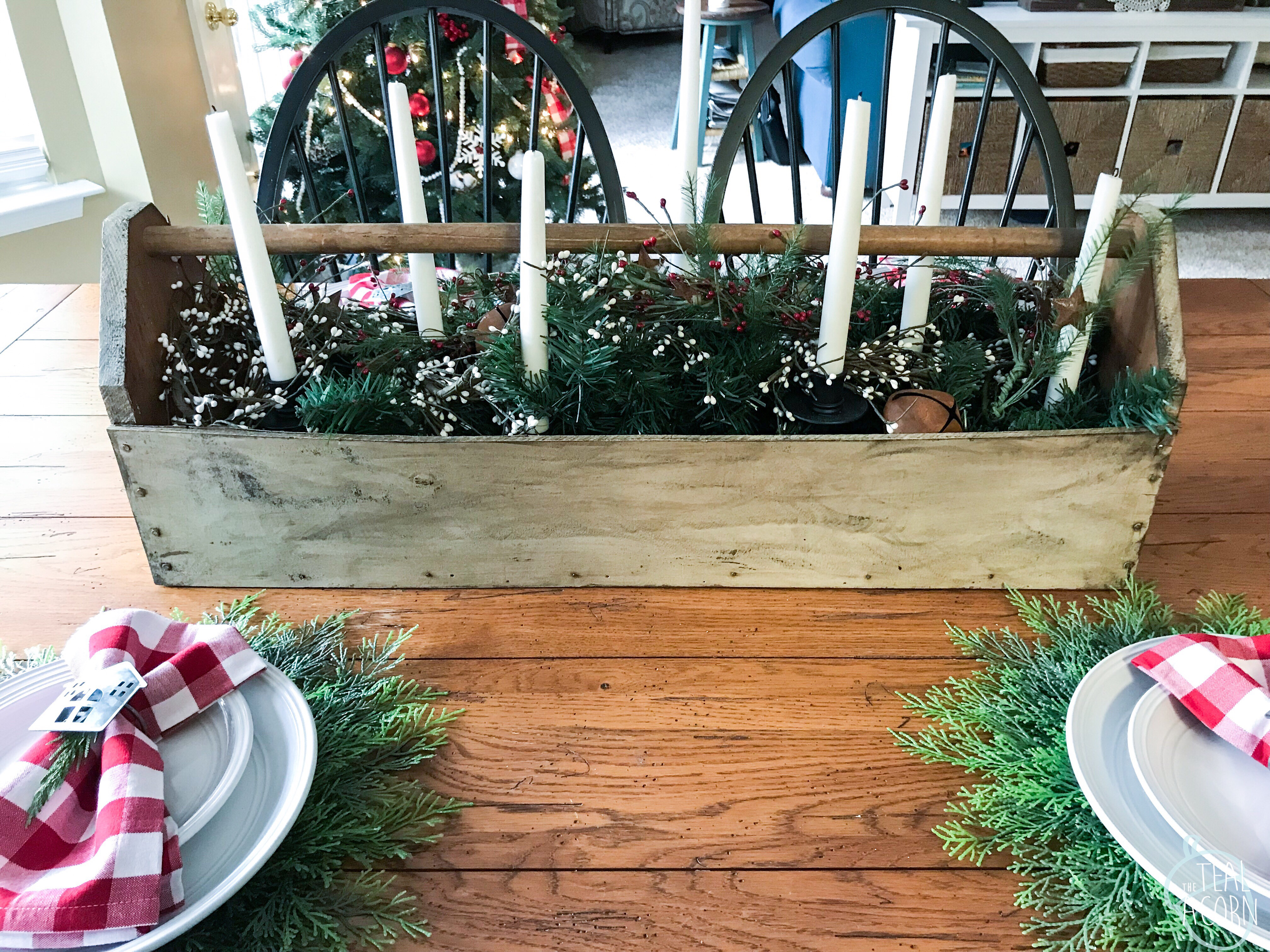 Farmhouse tables cape with vintage carpenter's toolbox as centerpiece filled with garland and candelabra and candlesticks.  Place settings have Pier 1 cypress chargers, white plates, red and white Buffalo check plaid napkins and galvanized metal napkin rings.