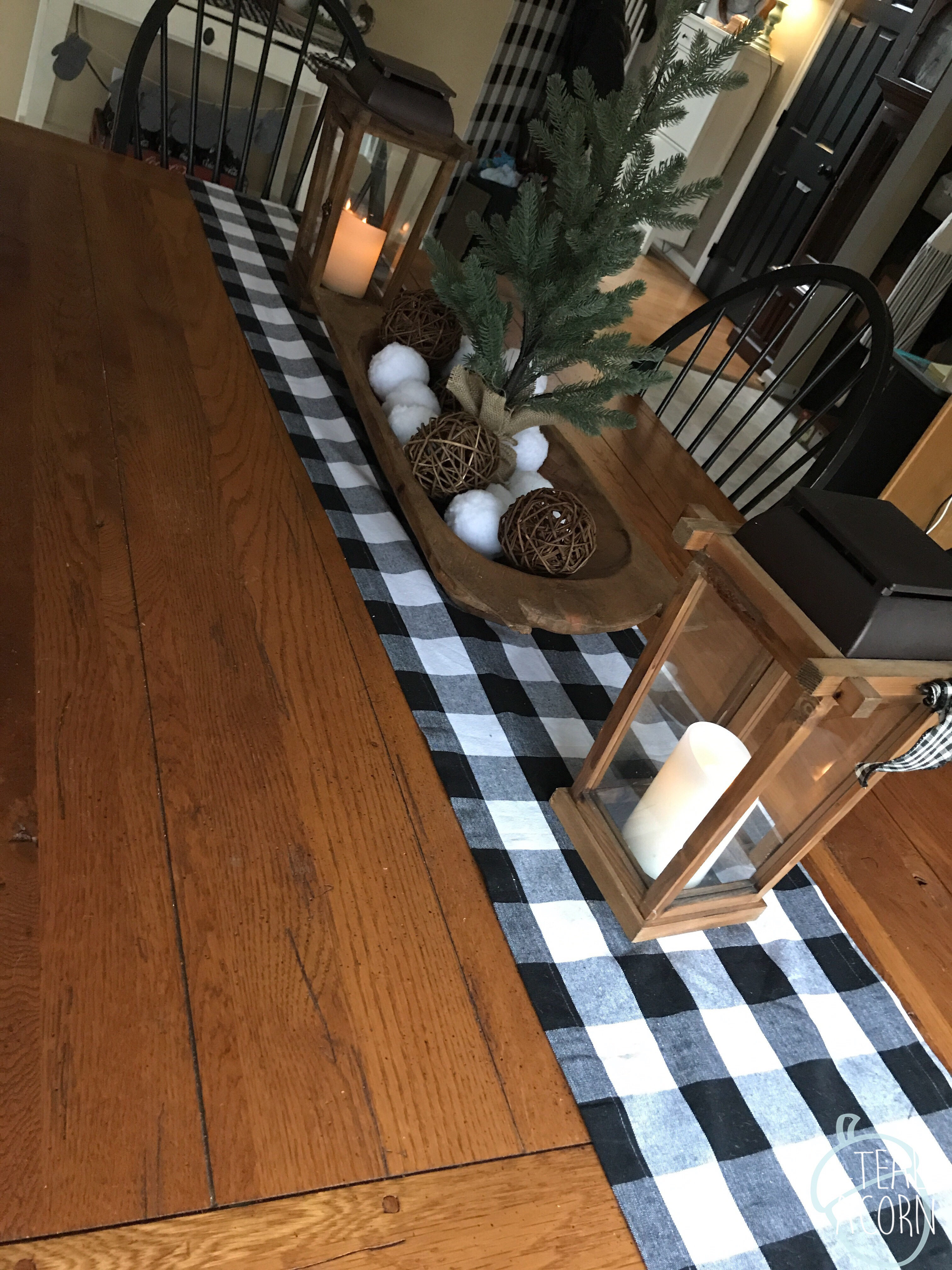 Large Farmhouse table with buffalo check runner, dough bowl, winter centerpiece, and wooden lanterns.  Ikea Hemnes Shoe cabinet iand diy buffalo check plaid accent wall n the background.