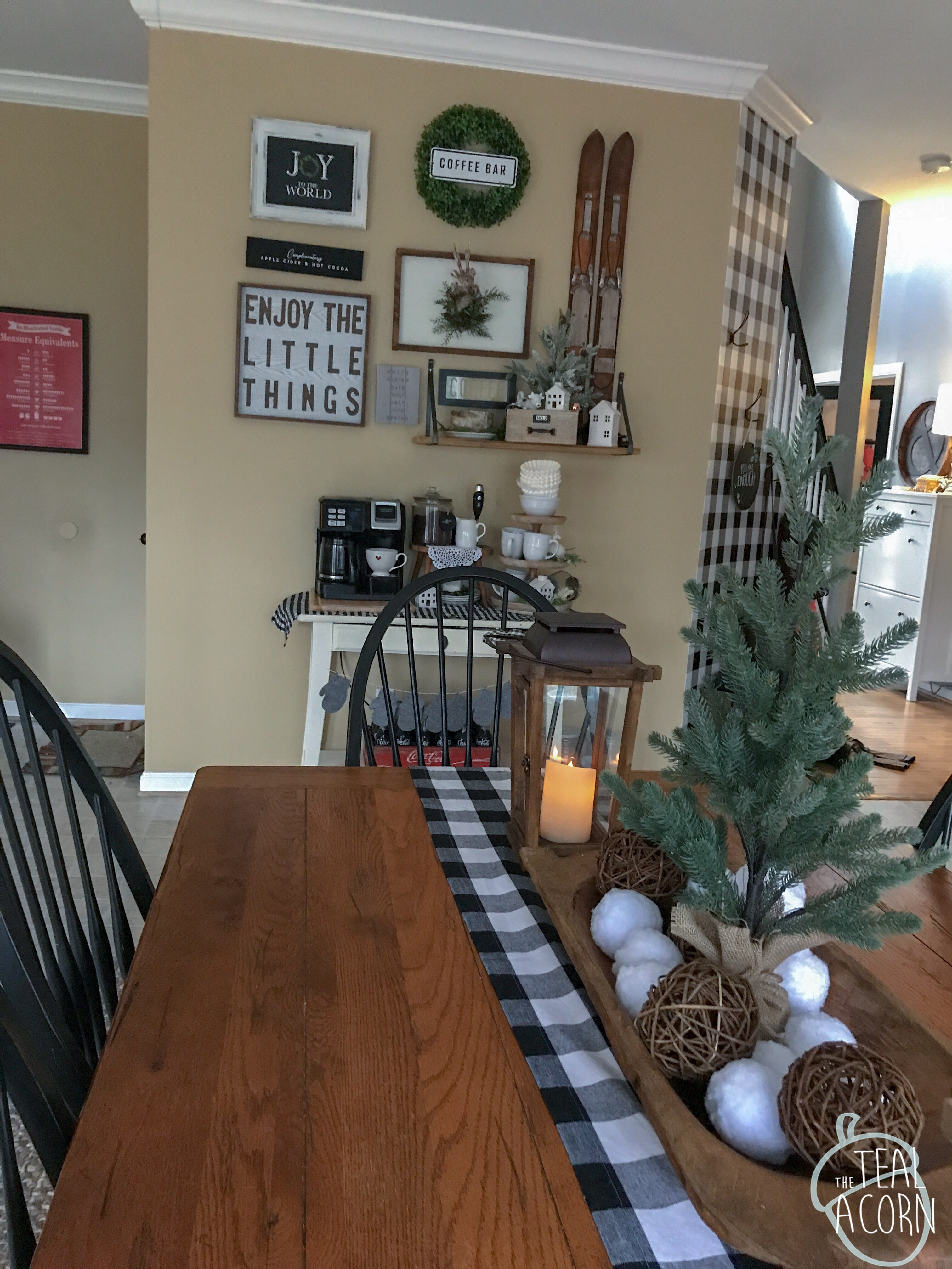 Winter gallery wall that changes seasonally. Farmhouse style signs located above a coffee bar. Large Farmhouse table with buffalo check runner, dough bowl, winter centerpiece, and wooden lanterns.  Ikea Hemnes Shoe cabinet iand diy buffalo check plaid accent wall n the background.