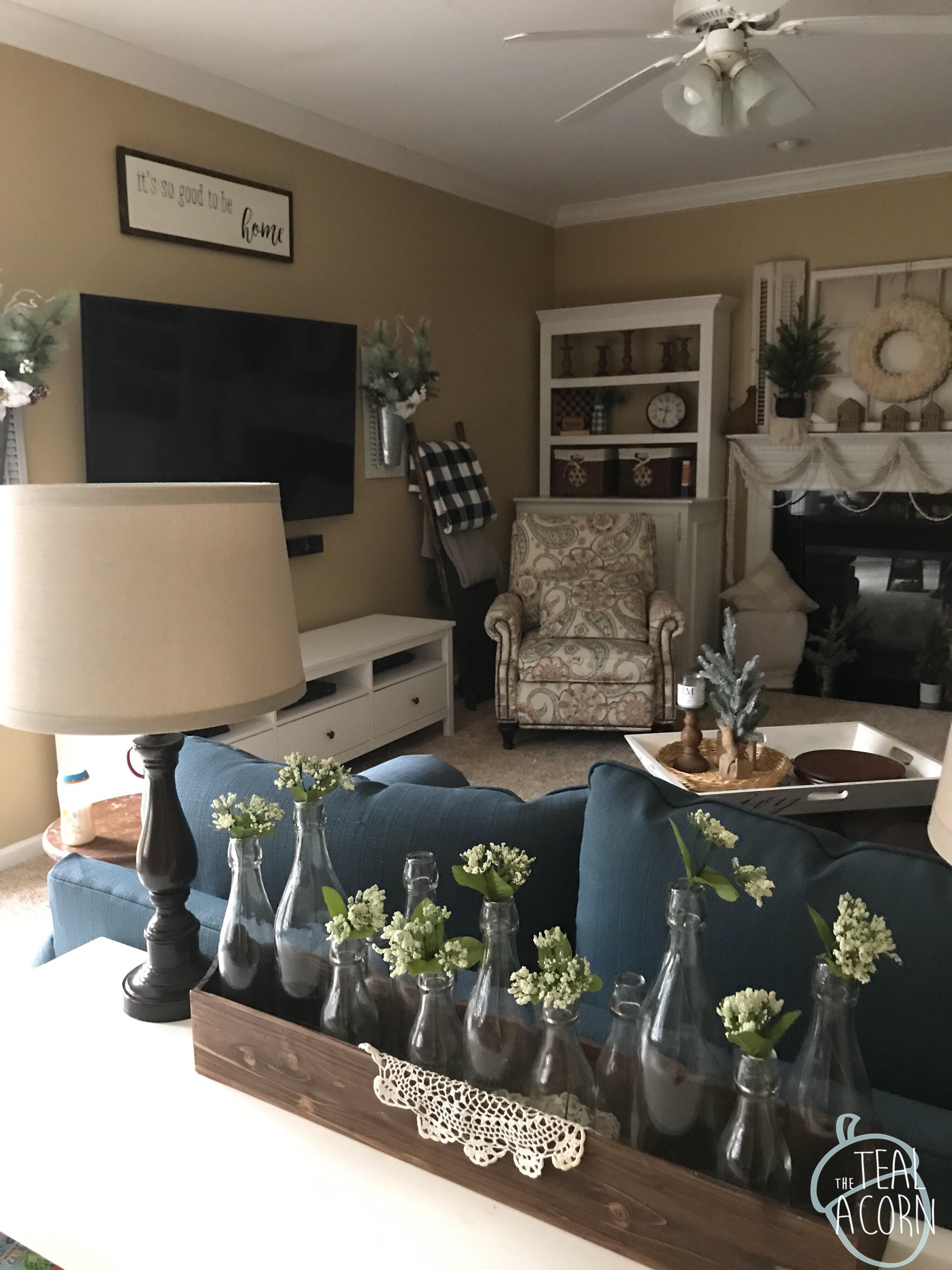 Winter decor in a farmhouse style family room with teal couch and printed armchair