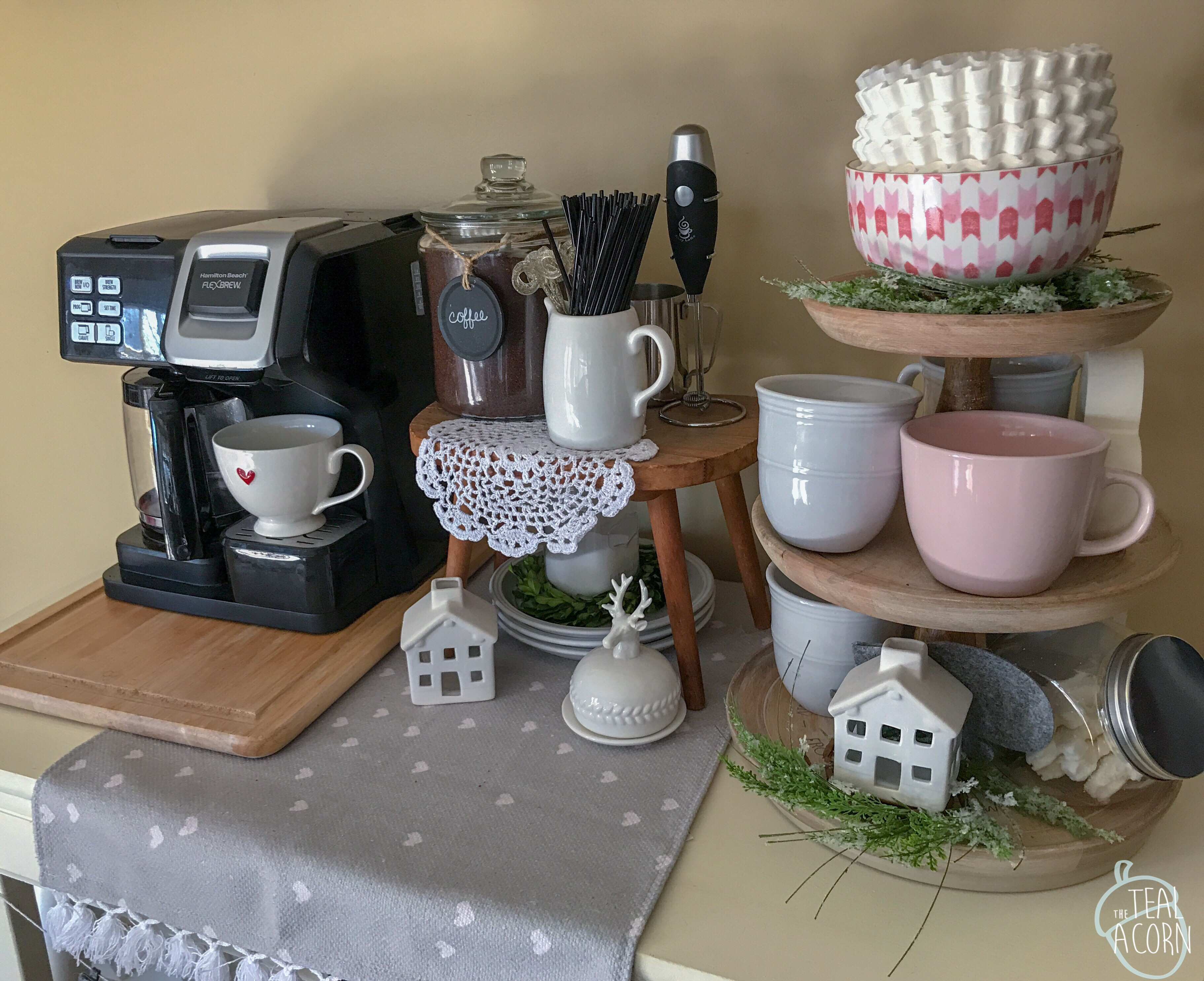 coffee bar decorated for valentines day with tiered tray decorated for valentines day with blush pink mugs, heart decor, and target dollar spot items.