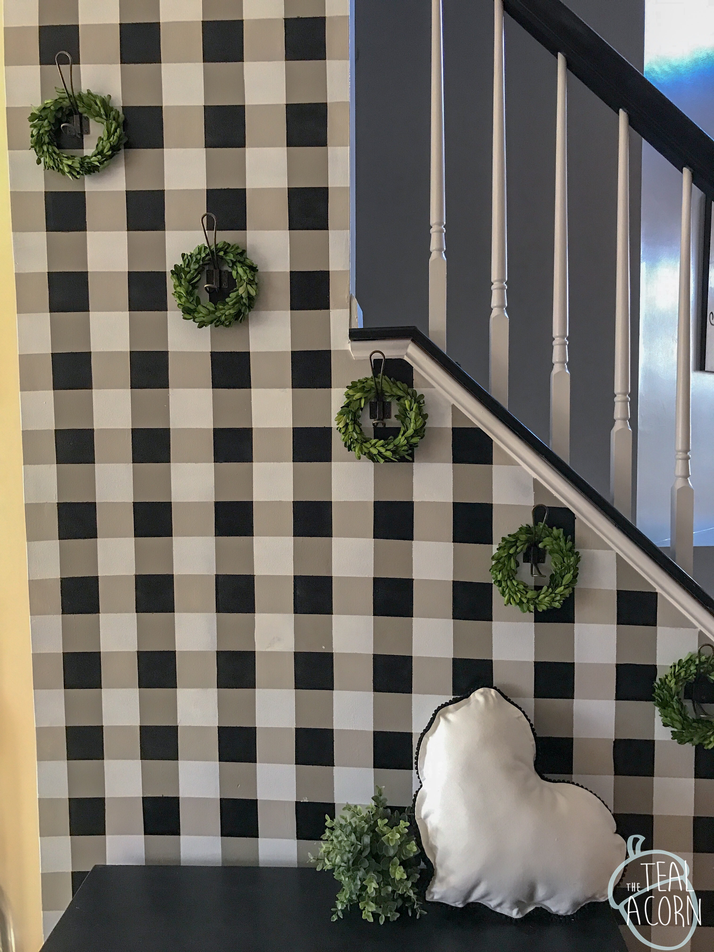 black and white Valentine's Day decor on a diy painted buffalo plaid wall with hooks and greenery.