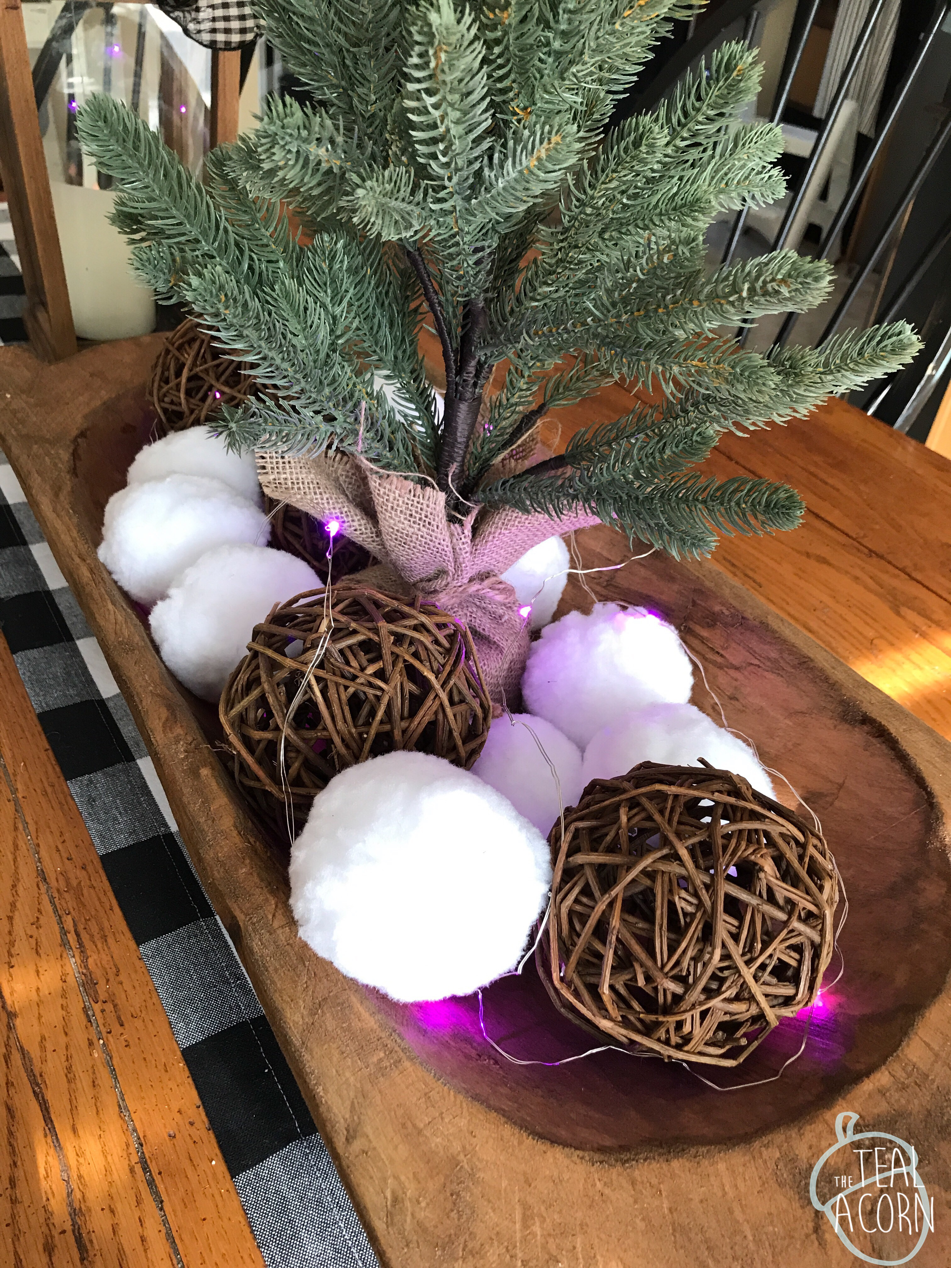 Decor steals dough bowl decorated for winter with faux snowballs and faux evergreen tree.  Pink fairy lights add a whimsical valentines day touch.