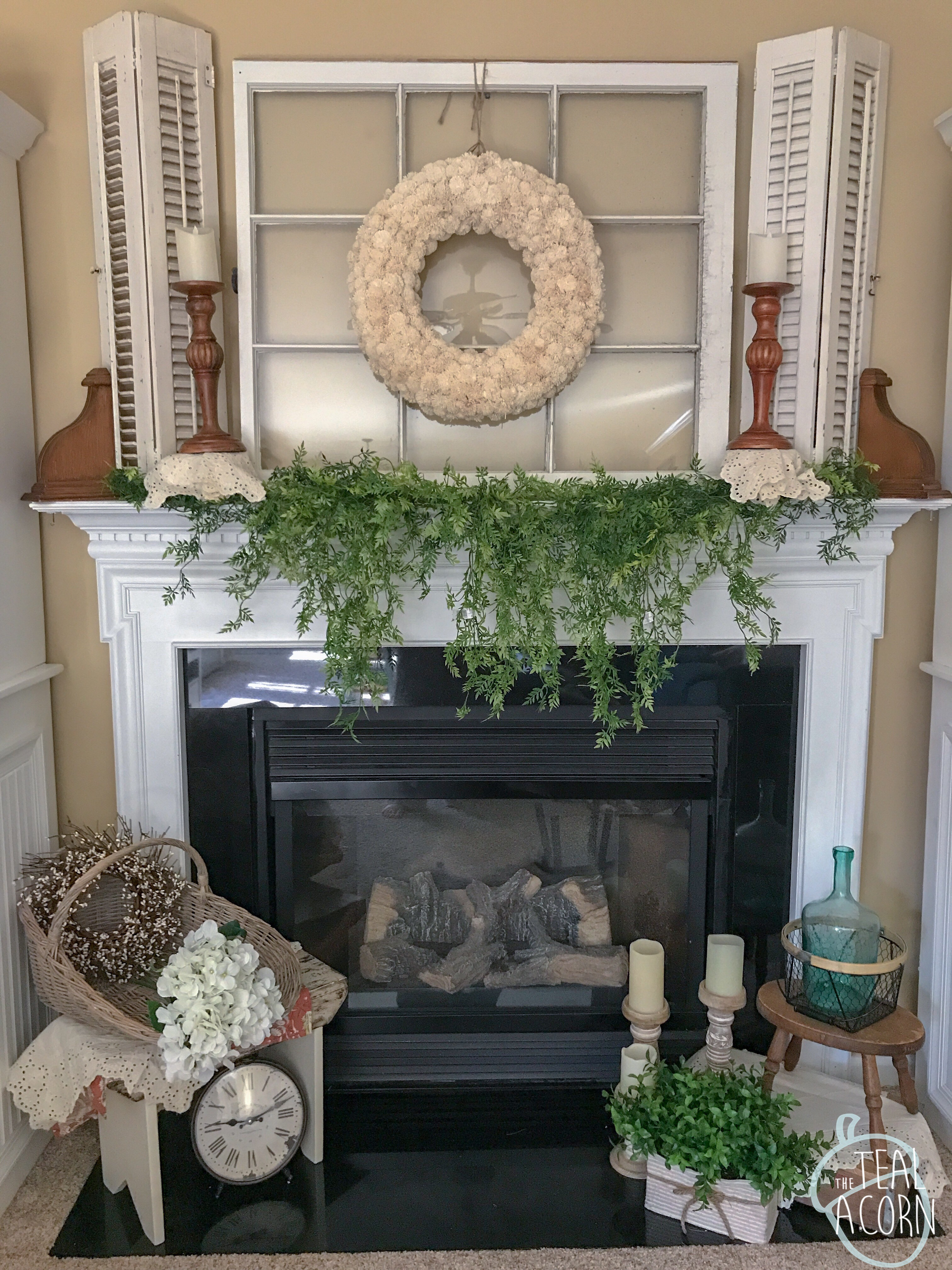 Spring mantle with draping ficus greenery, old window above mantle, and old shutters above mantle