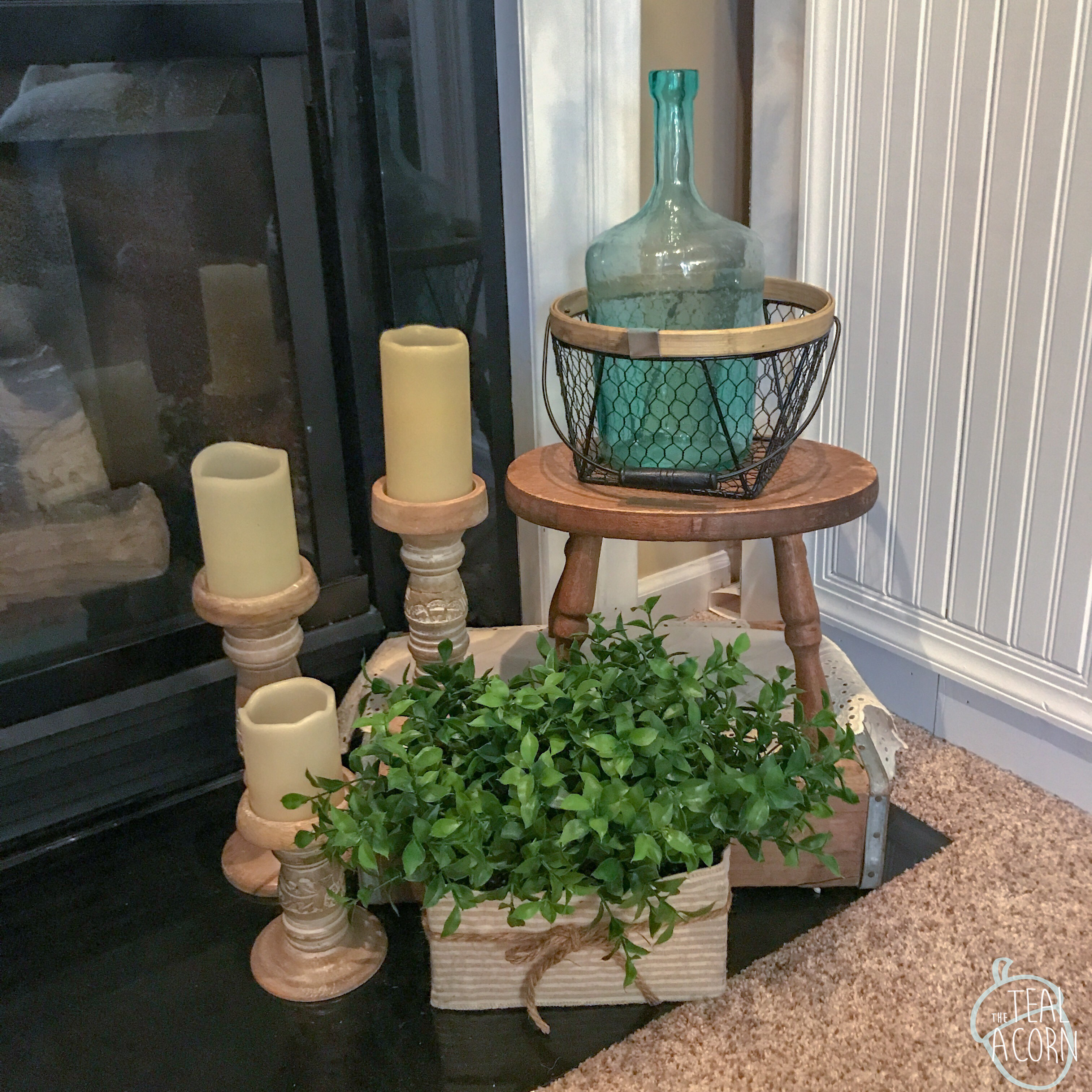 Hearth spring mantle decor with old soda crate, wooden stool, wooden candle sticks, blue green jug, and chicken wire basket